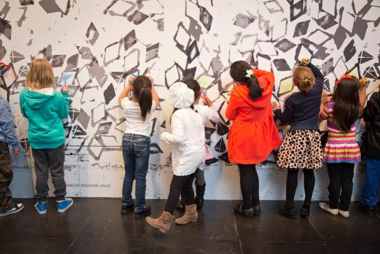 Students at a Paries Pictus workshop colouring in Robin Rhode's Rough cut (2007)
