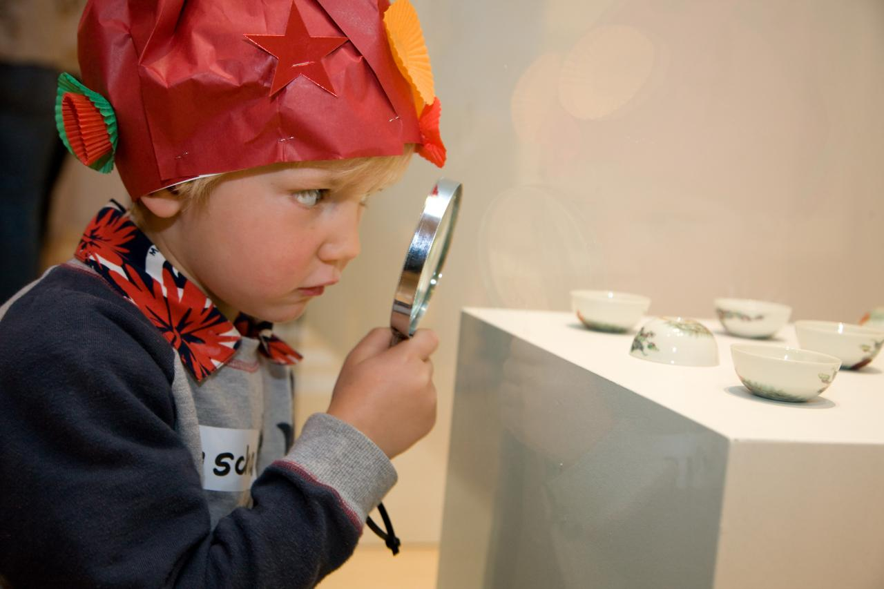 A young boy takes the NGV Kids Activity Trail through the exhibition 'The cricket and the dragon: animals in Asian art' at NGV International.