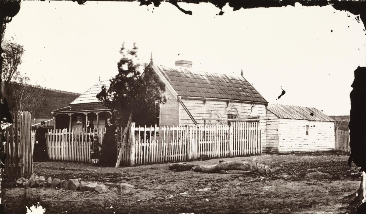 No title (Family outside weatherboard house with slate roof)