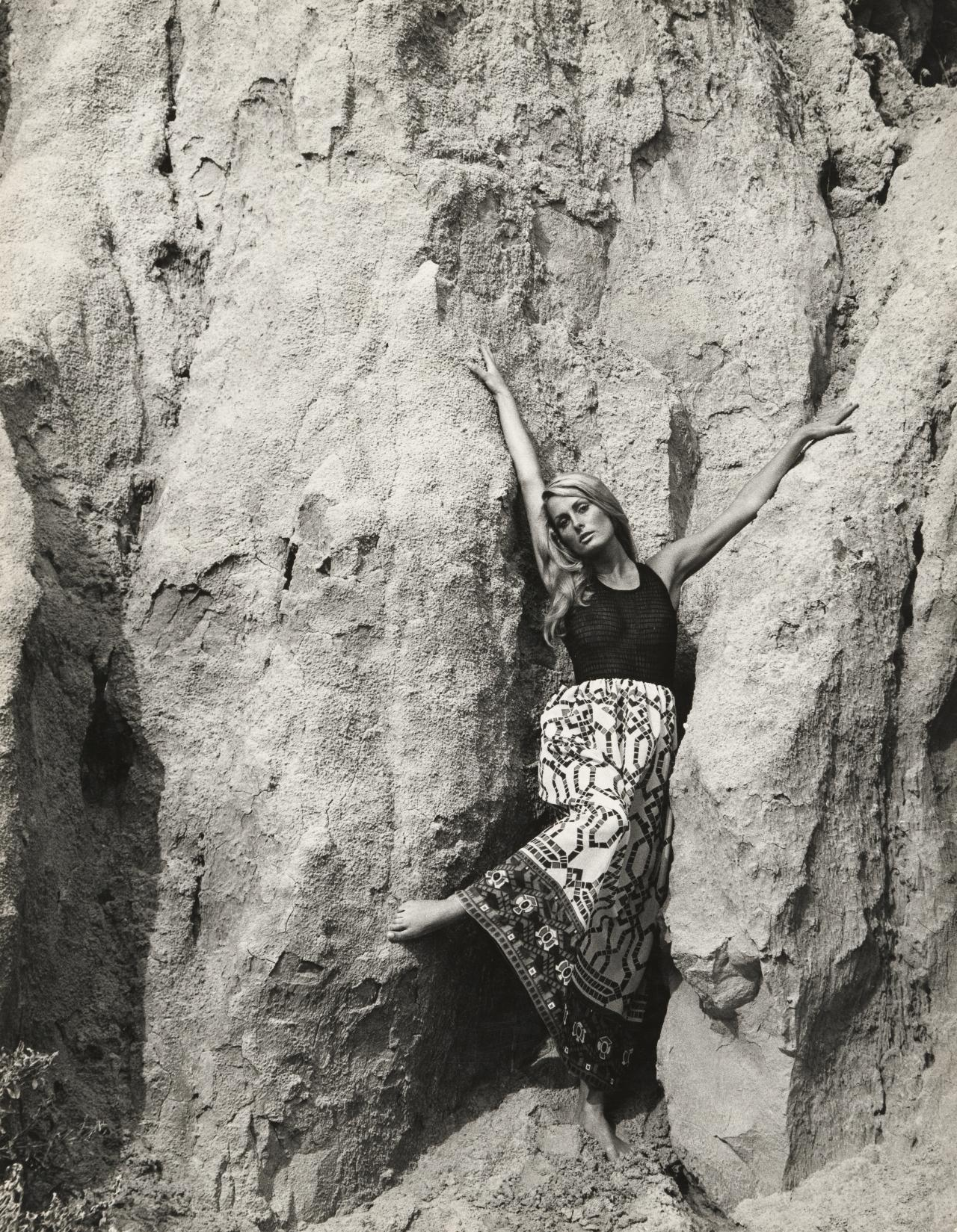 No title (Fashion illustration. Model in long printed skirt against cliff)