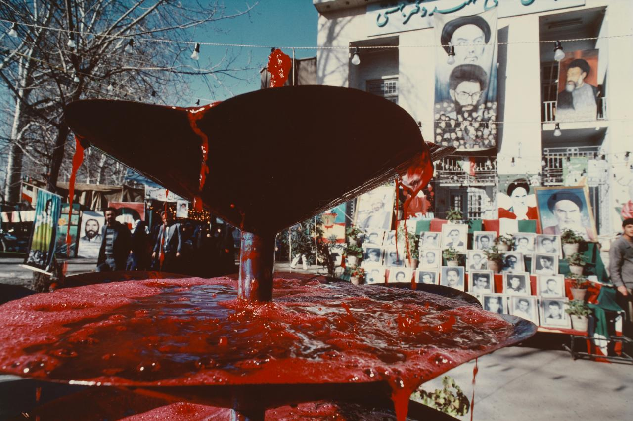 A martyrs' fountain in the centre of Mashad bubbles with red-dyed water - a symbol of the blood of the martyrs.  Behind the fountain photographs of local martyrs form a shrine
