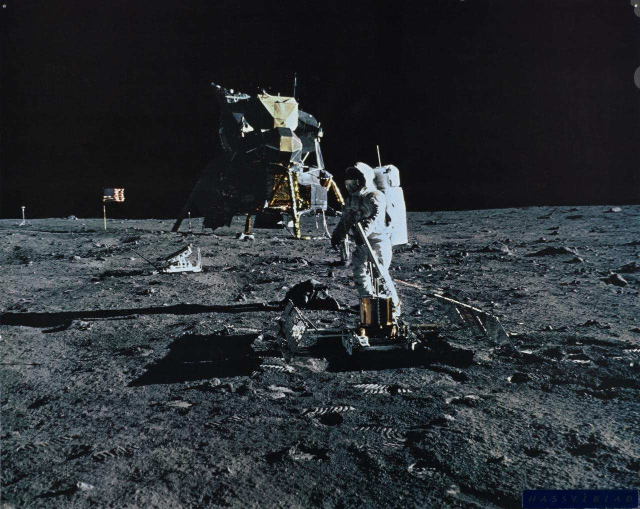 Aldrin setting out seismometer near module, U.S.A. flag in background