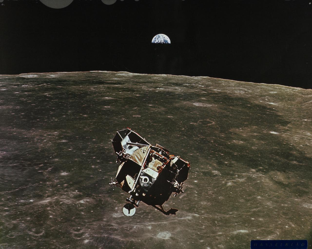 Lunar module ascending from moon earth in background