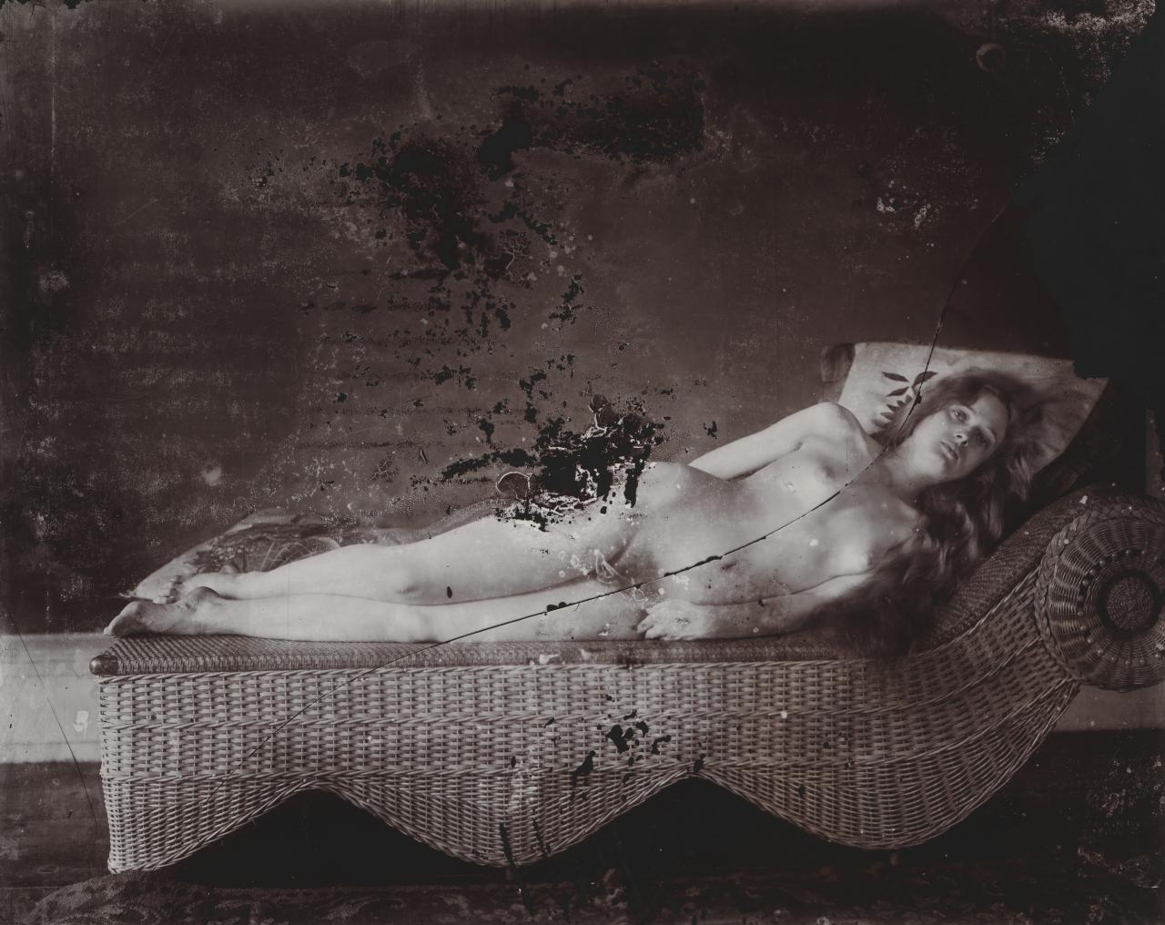 No title (Woman reclining on rattan couch)