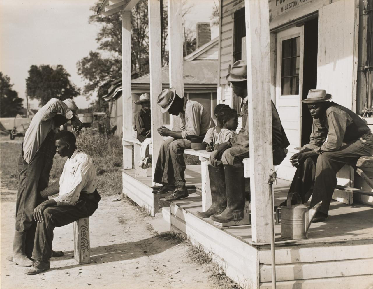 Haircutting in front of plantation store after being paid off on Saturday, Mileston Plantation, Mississippi Delta