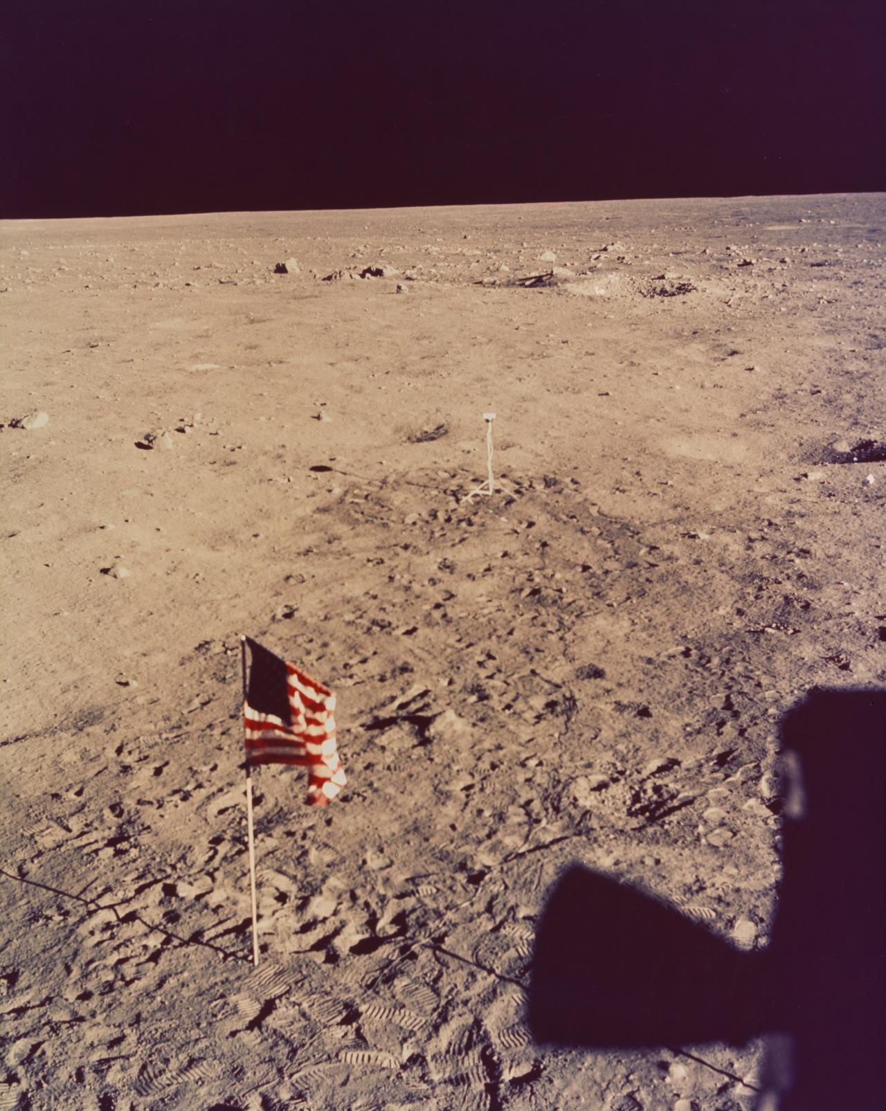 United States flag on moon surface with lunar surface television camera in background
