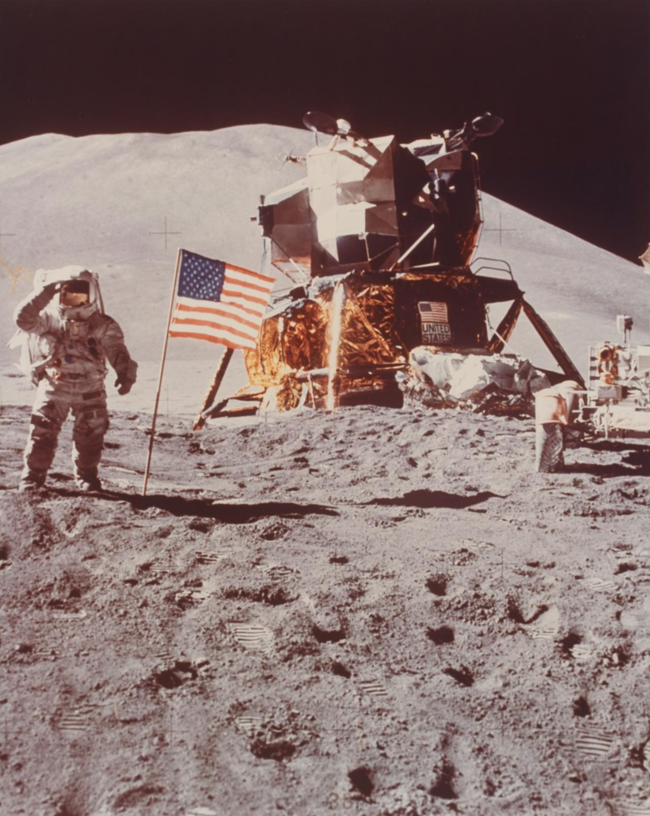 Apollo 15 mission. Astronaut Irwin saluting flag with lunar module, rover and hadley delta in background
