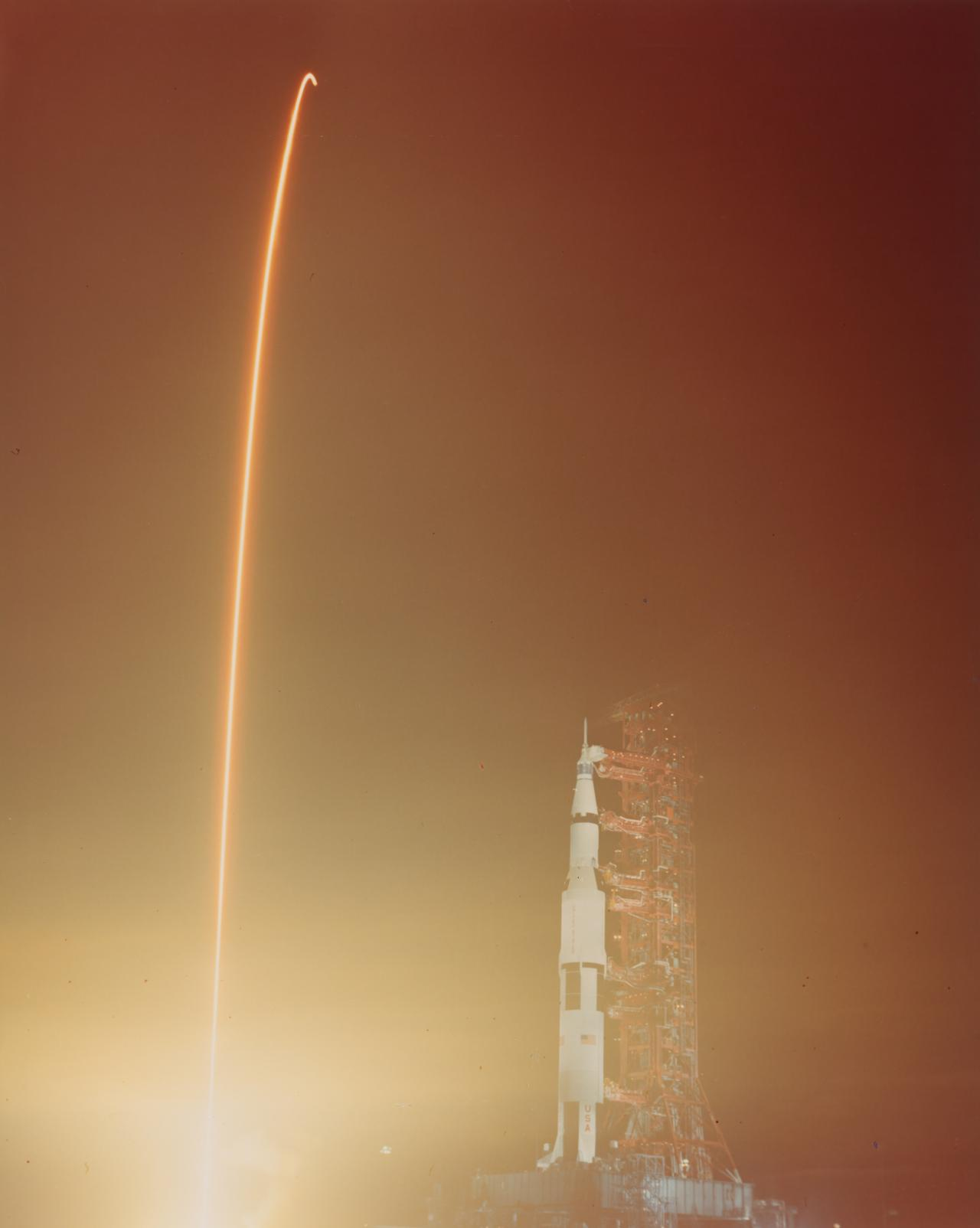 Composite photo, Apollo 17 on launch pad and streak exposure of lift-off EST 7 December 1972