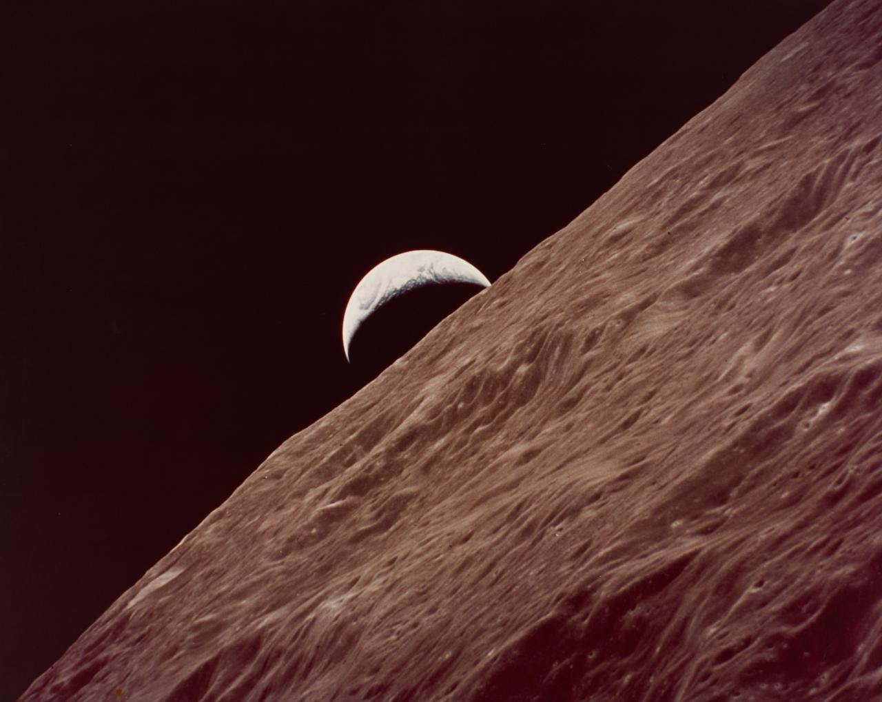Crescent Earth rises over lunar far side, seen from Apollo 17