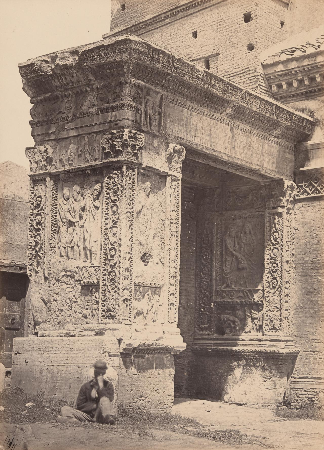 No title (Man sitting at base of carved porch of buttress)